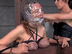 Plastic wrapped around the head of a cute bondage slut