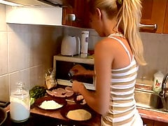 Pretty blonde Sophie Moone cooks breakfast in the kitchen
