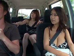 Two busty Japanese girls give a titjob to some guy in a car